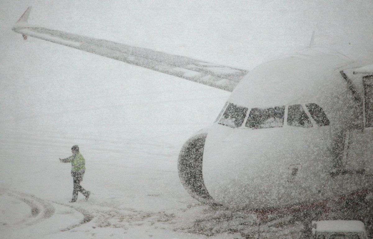 A worker walks past a plane parked on the snow covered tarmac of Zurich airport in Kloten after the region was hit by strong snow falls, December 17, 2010. REUTERS/Christian Hartmann (SWITZERLAND - Tags: ENVIRONMENT TRANSPORT) (Reuters)