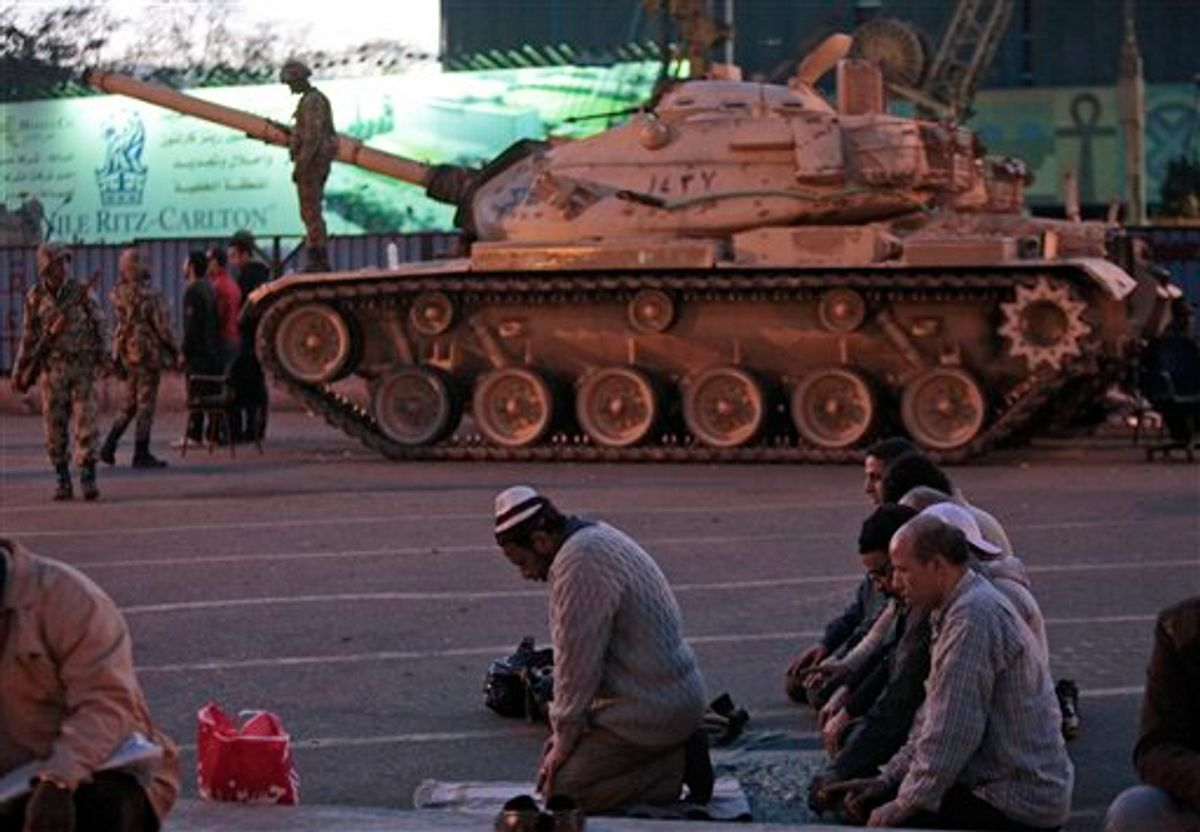 Anti-government protesters offer their evening prayers, in front of an Egyptian army tank securing the area, during a protest in Cairo's Tahrir Square, Egypt, Monday, Jan. 31, 2011. A coalition of opposition groups called for a million people to take to Cairo's streets Tuesday to demand the removal of Egyptian President Hosni Mubarak. (AP Photo/Lefteris Pitarakis) (AP)