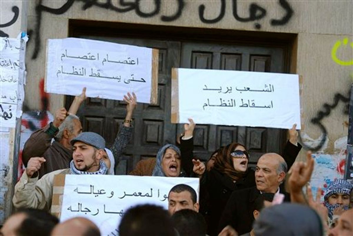 """This photograph, obtained by The Associated Press outside Libya and taken by an individual not employed by AP, shows people chanting and holding signs during recent days' unrest in Benghazi, Libya.  Placards in Arabic read at top left """"Strike, strike until the fall of the regime"""", and at top right """"The people want to topple the regime"""".  (AP Photo) EDITOR'S NOTE: THE AP HAS NO WAY OF INDEPENDENTLY VERIFYING THE EXACT CONTENT, LOCATION OR DATE OF THIS IMAGE. (AP)"""