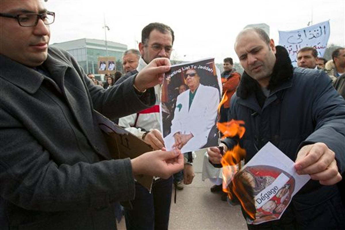 Protesters burn photos of Libyan leader Moammar Ghaddafi during a demonstration to support the Libyan people, on Place des Nations in front of the European headquarters of the United Nations, in Geneva, Switzerland, Saturday, Feb. 19, 2011. (AP Photo/Keystone, Salvatore Di Nolfi) (AP)