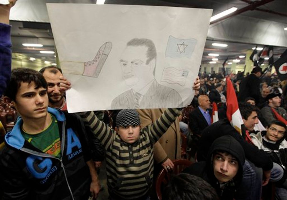 A youth holds a drawing depicting Egyptian President Hosni Mubarak during a speech by Hezbollah leader Hassan Nasrallah at a ceremony called for by Lebanese anti-American groups to support anti-government protesters in Egypt, in Beirut, Lebanon, Monday, Feb. 7, 2011. Speaking on a screen Nasrallah said the Egyptian uprising will change the Mideast for generations to come. (AP Photo/Bilal Hussein) (AP)