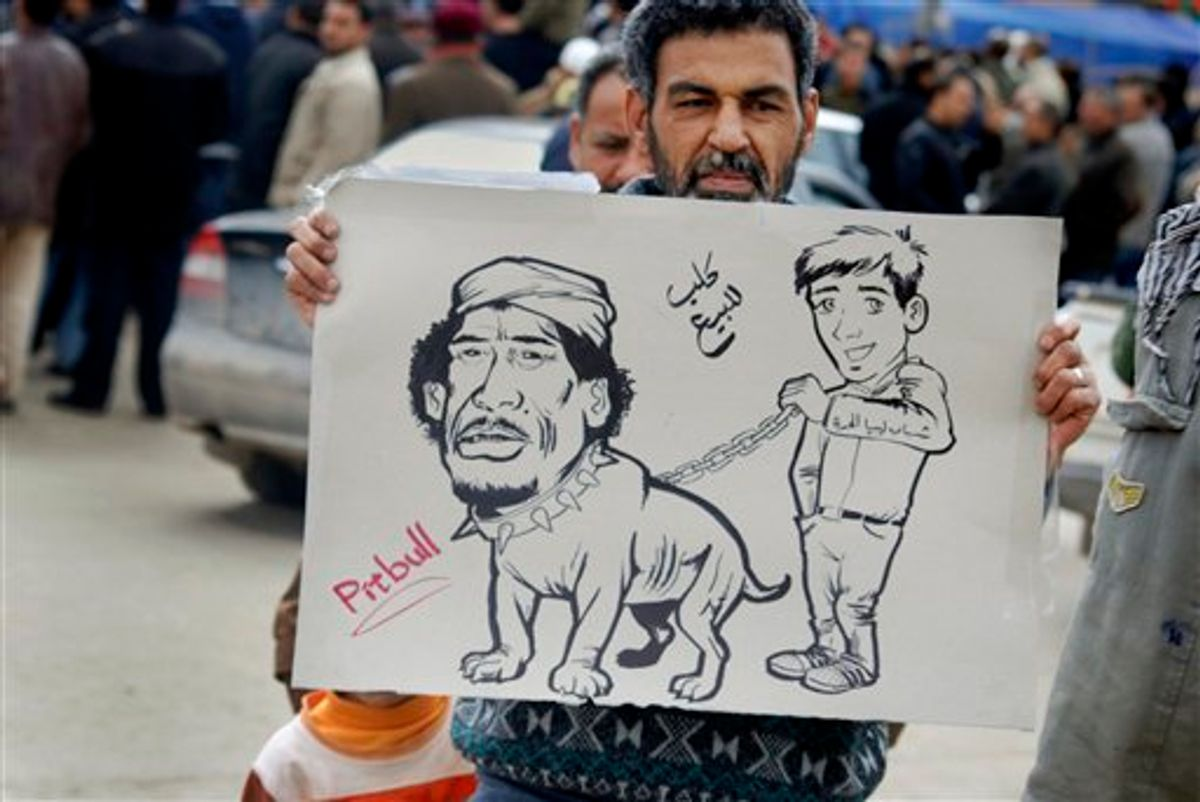 """A protester holds a placard portraying Libyan Leader Moammar Gadhafi as a pitbull dog held on a chain by a youth, with writing in arabic reading """"Dog for sale"""" and on arm of youth """"Youth of Free Libya"""", in Benghazi, Libya Wednesday, Feb. 23, 2011. Militiamen loyal to Moammar Gadhafi clamped down in Tripoli Wednesday, but cracks in his regime spread elsewhere across the nation, as the protest-fueled rebellion controlling much of eastern Libya claimed new gains closer to the capital. (AP Photo/Alaguri) (AP)"""