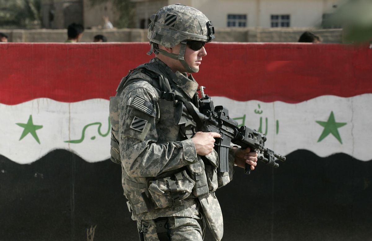 A U.S. soldier of Charlie Company 1-15 Infantry, 3rd Brigade Combat team, 3rd Infantry Division, passes next to a wall painted with the Iraqi flag during a routine patrol in Salman Pak, about 30 miles (45 kilometers) south of Baghdad, Iraq, Saturday, March 1, 2008. (AP Photo/Petros Giannakouris) (Associated Press)