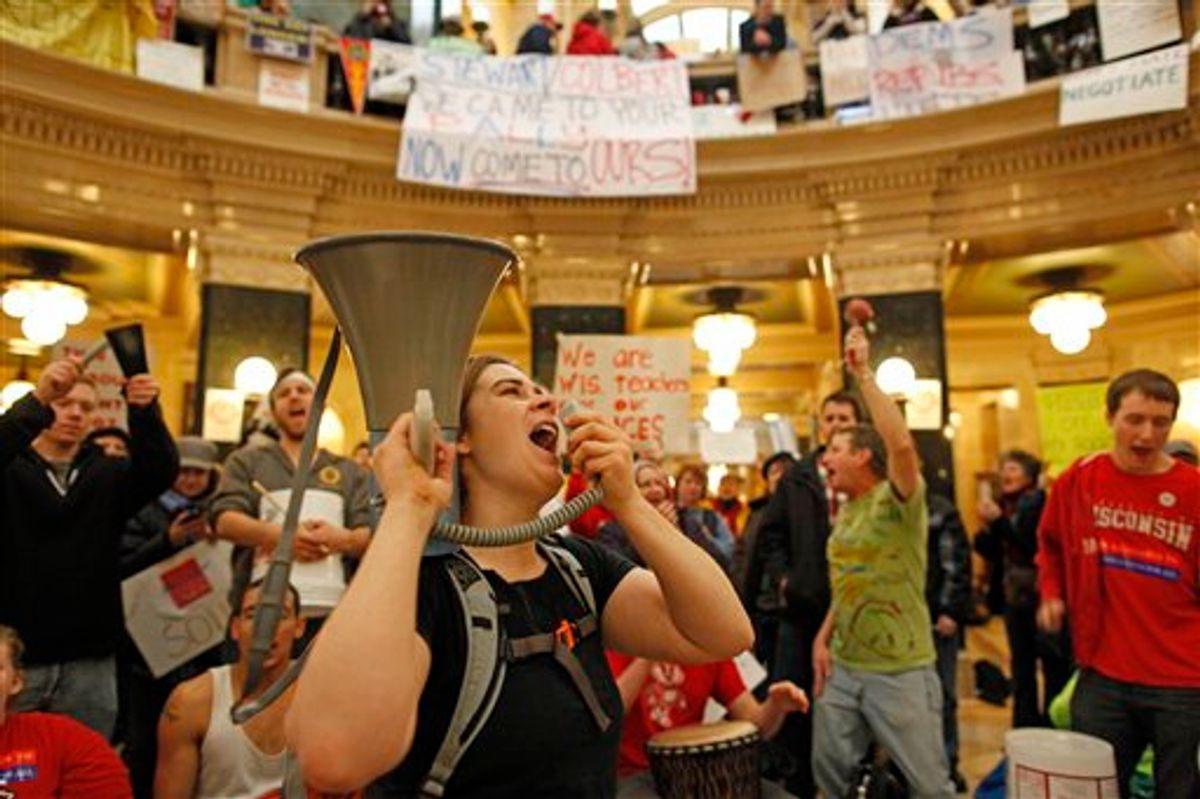 Protesters bang drums and shout slogans inside the state Capitol Monday, Feb. 21, 2011, in Madison, Wis. Opponents to Gov. Scott Walker's bill to eliminate collective bargaining rights for many state workers are taking part in their seventh day of protesting.  (AP Photo/Jeffrey Phelps) (AP)