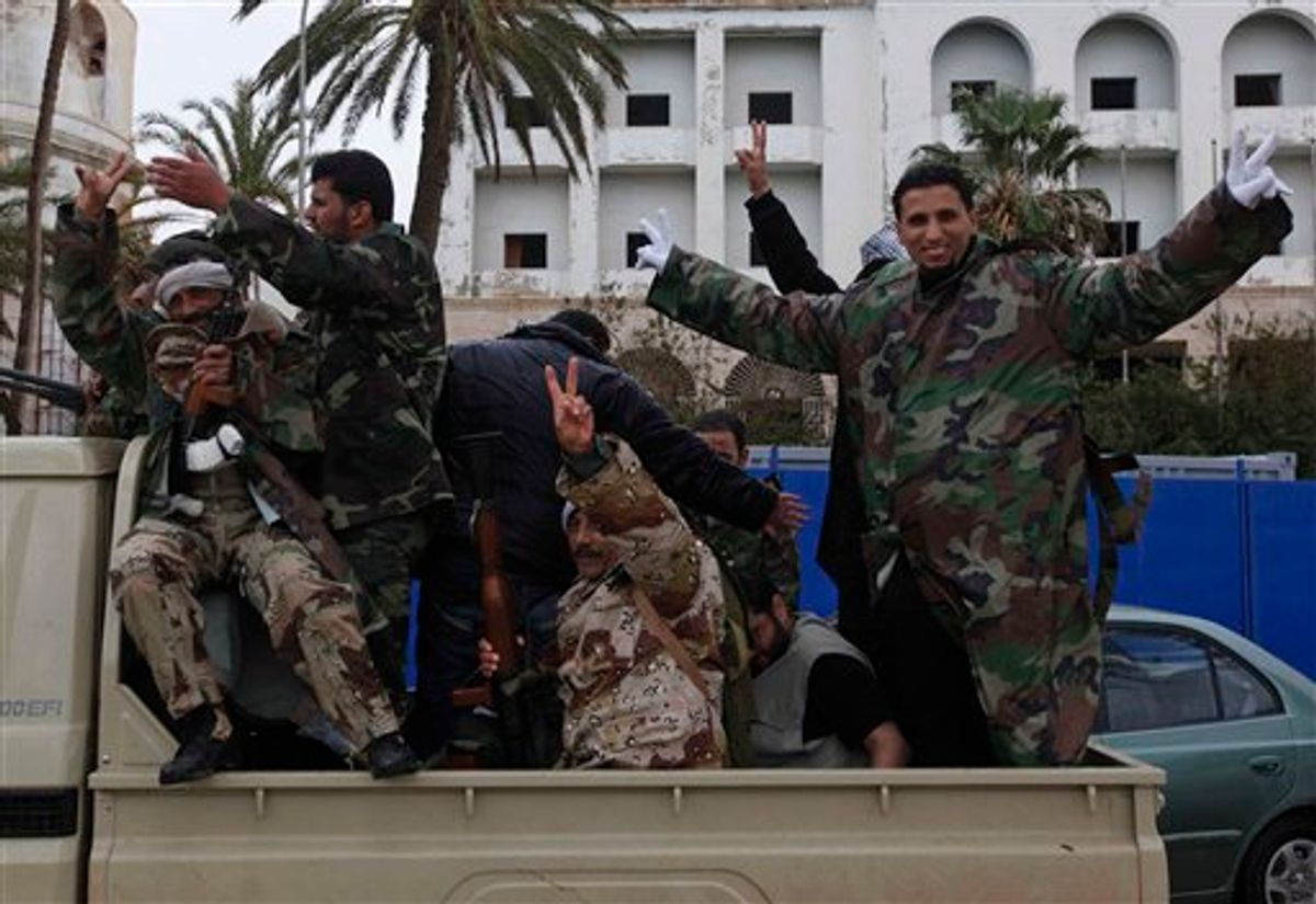 Libyan gunmen flash the V sign as they stand on a military vehicle driving in the streets of  Benghazi, Libya, on Friday Feb. 25, 2011. Several tens of thousands held a rally in support of the Tripoli protesters in the main square of Libya's second-largest city, Benghazi, where the revolt began, about 580 miles (940 kilometers) east of the capital along the Mediterranean coast.  (AP Photo/Hussein Malla) (AP)