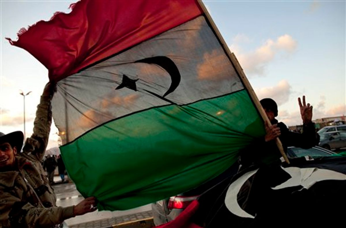 Libyan men hold the former royal flag as they drive past a demonstration against Libyan leader Moammar Gadhafi in Benghazi, in eastern Libya, Sunday, Feb. 27, 2011. (AP Photo/Kevin Frayer) (AP)