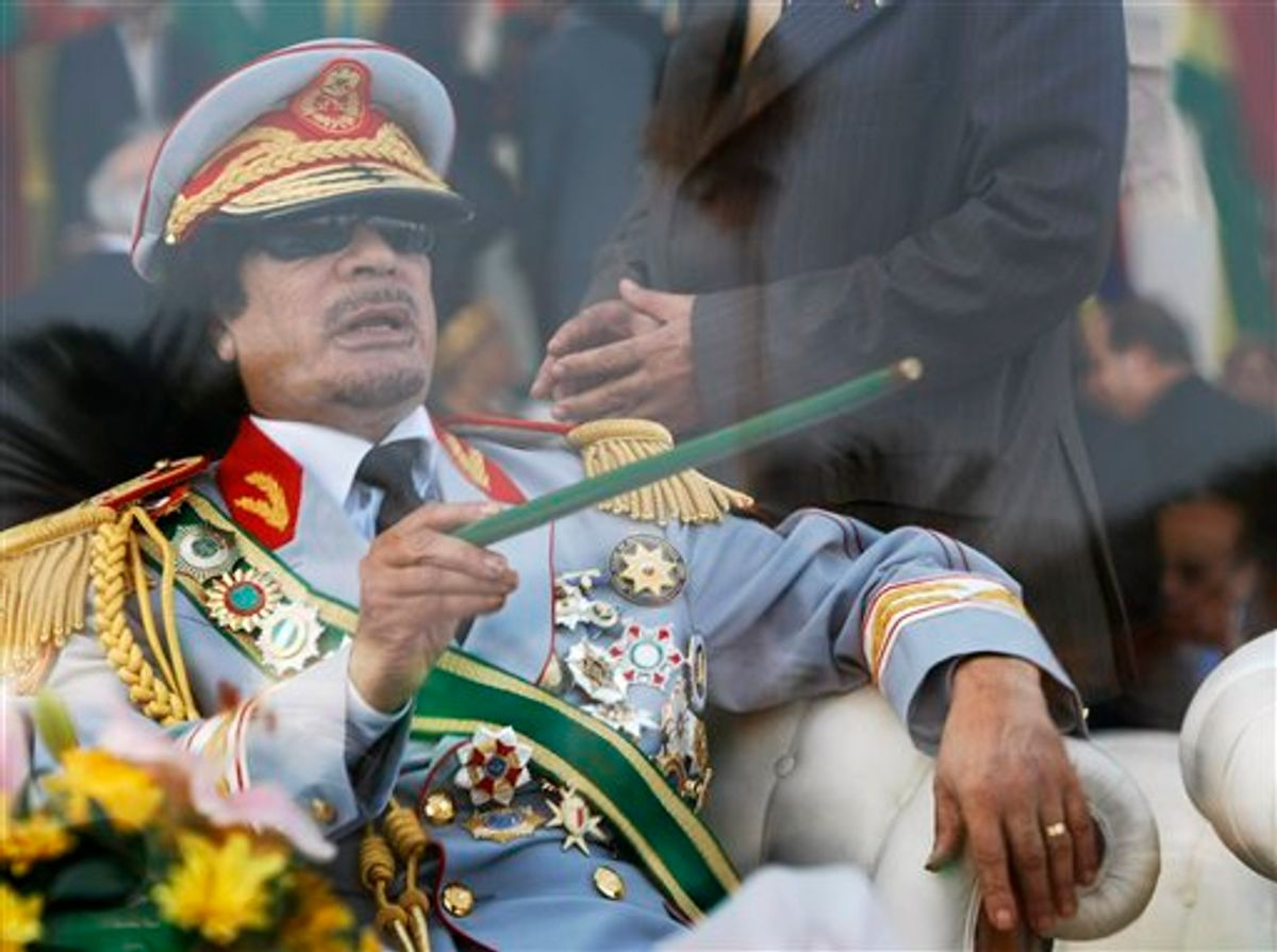 """FILE - In this Sept. 1, 2009 file photo, Libyan leader Moammar Gadhafi gestures with a green cane as he takes his seat behind bulletproof glass for a military parade in Green Square, Tripoli, Libya. Libyan protesters celebrated in the streets of Benghazi on Monday, Feb. 21, 2011 claiming control of the country's second largest city after bloody fighting, and anti-government unrest spread to the capital with clashes in Tripoli's main square for the first time. Moammar Gadhafi's son vowed that his father and security forces would fight """"until the last bullet."""" (AP Photo/Ben Curtis, FIle) (AP)"""