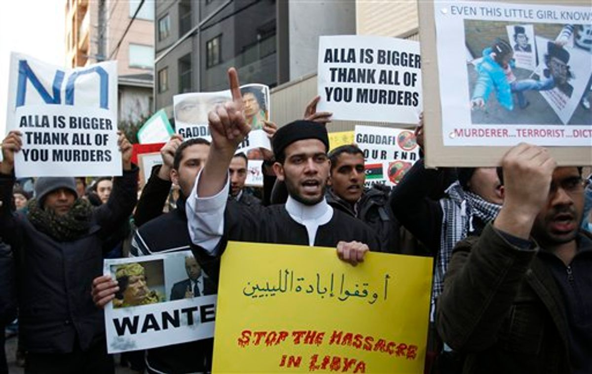 Libyans living in Japan and their supporters shout slogans against Libyan leader Moammar Gadhafi in front of the Libyan embassy in Tokyo, on Wednesday, Feb. 23, 2011. (AP Photo/Shizuo Kambayashi) (AP)