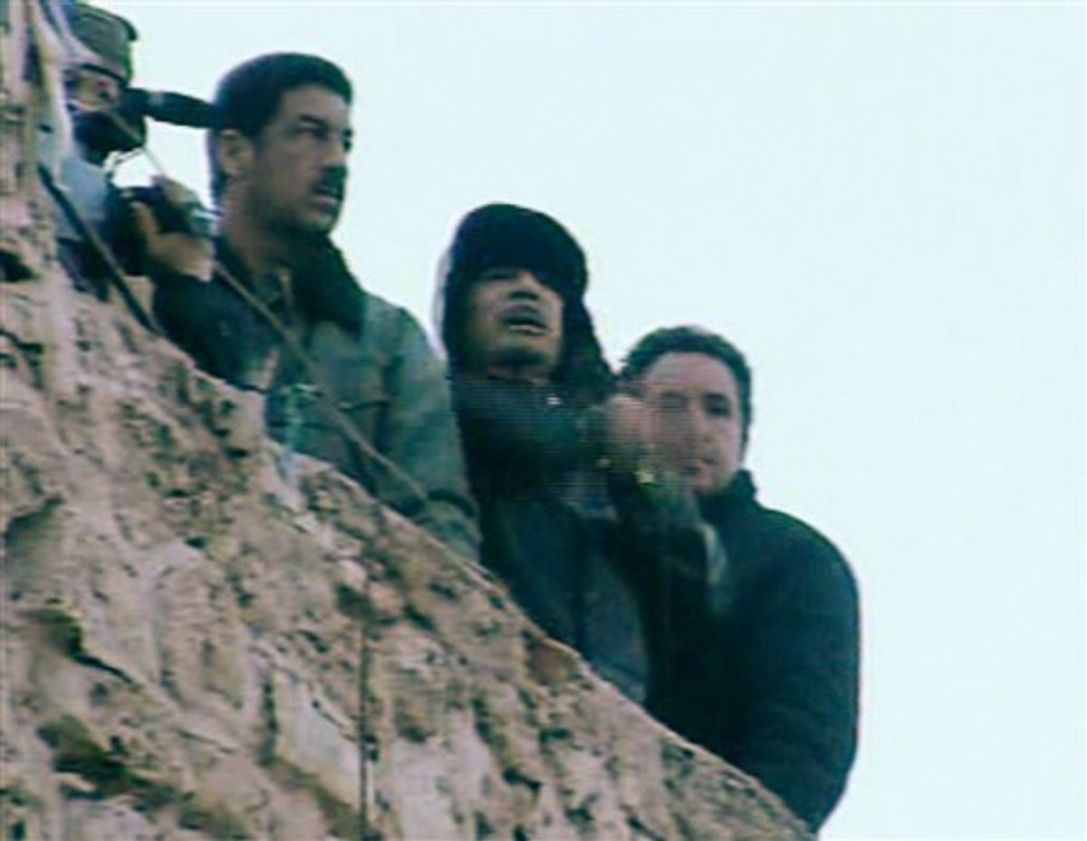 In this image taken from Libya State Television, showing Libyan leader Moammar Gadhafi, centre, as he speaks to followers from the top of a stone wall at The Green Square, central Tripoli, Libya, Friday, Feb. 25, 2011.  The TV station declared this to be a live broadcast from the square and also showed a large crowd celebrating in the square below.  (AP Photo/Libya State) TV OUT (AP)