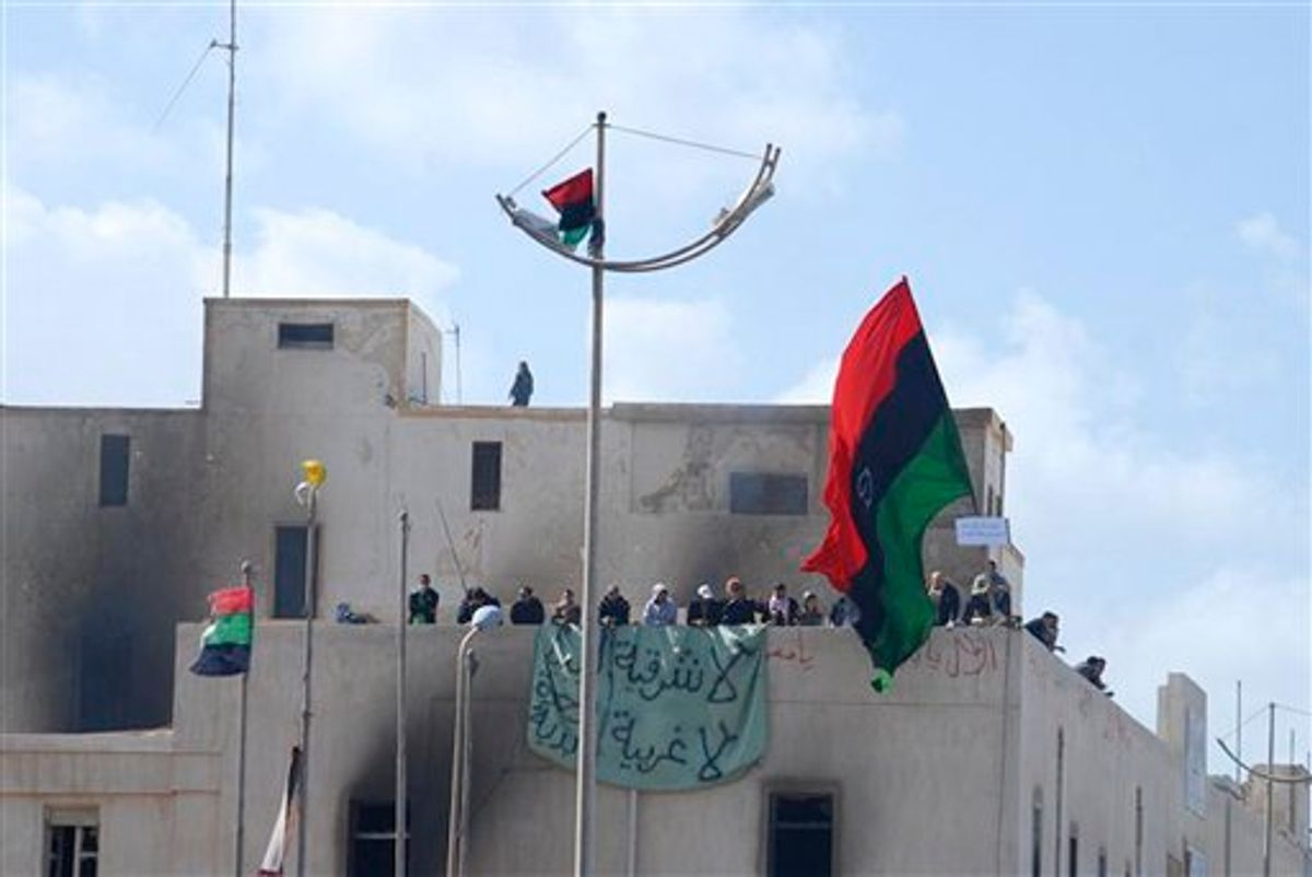 """This photograph, obtained by The Associated Press outside Libya and taken by an individual not employed by AP, shows people atop a building holding a banner and a flag during recent days' unrest in Benghazi, Libya. The graffiti in Arabic reads """"No to the East, no to the West"""".  (AP Photo) EDITOR'S NOTE: THE AP HAS NO WAY OF INDEPENDENTLY VERIFYING THE EXACT CONTENT, LOCATION OR DATE OF THIS IMAGE. (AP)"""