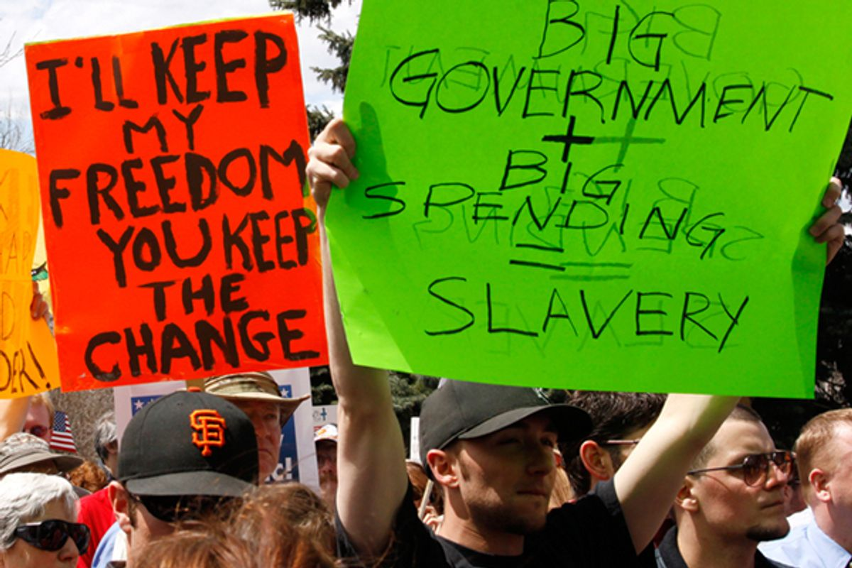 People wave signs at a Tea Party protest on the grounds of the Colorado state Capitol in Denver on April 15, 2009.