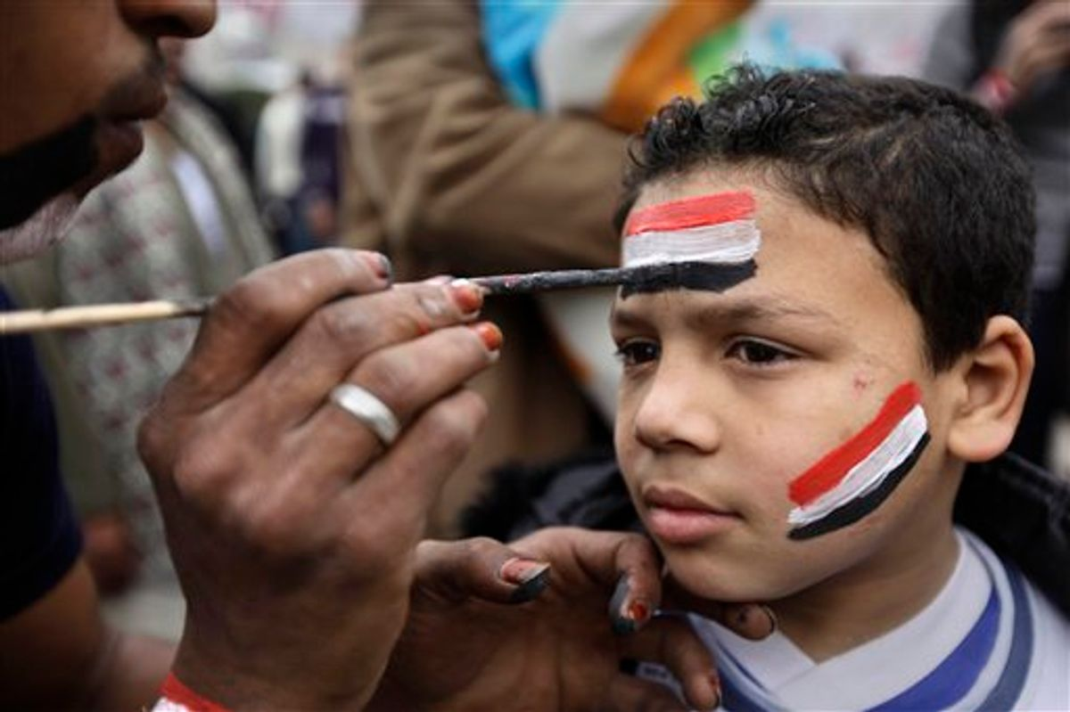 A young anti-government protester has his face painted in the colors of the Egyptian flag at the continuing protest in Tahrir Square in downtown Cairo, Egypt, Monday, Feb. 7, 2011. Egypt's embattled regime announced Monday a 15 percent raise for government employees in an attempt to shore up its base and defuse popular anger but the gestures so far have done little to persuade the tens of thousands of protesters occupying Tahrir Square to end their two-week long protest, leaving the two sides in an uneasy stalemate. (AP Photo/Ben Curtis) (AP)