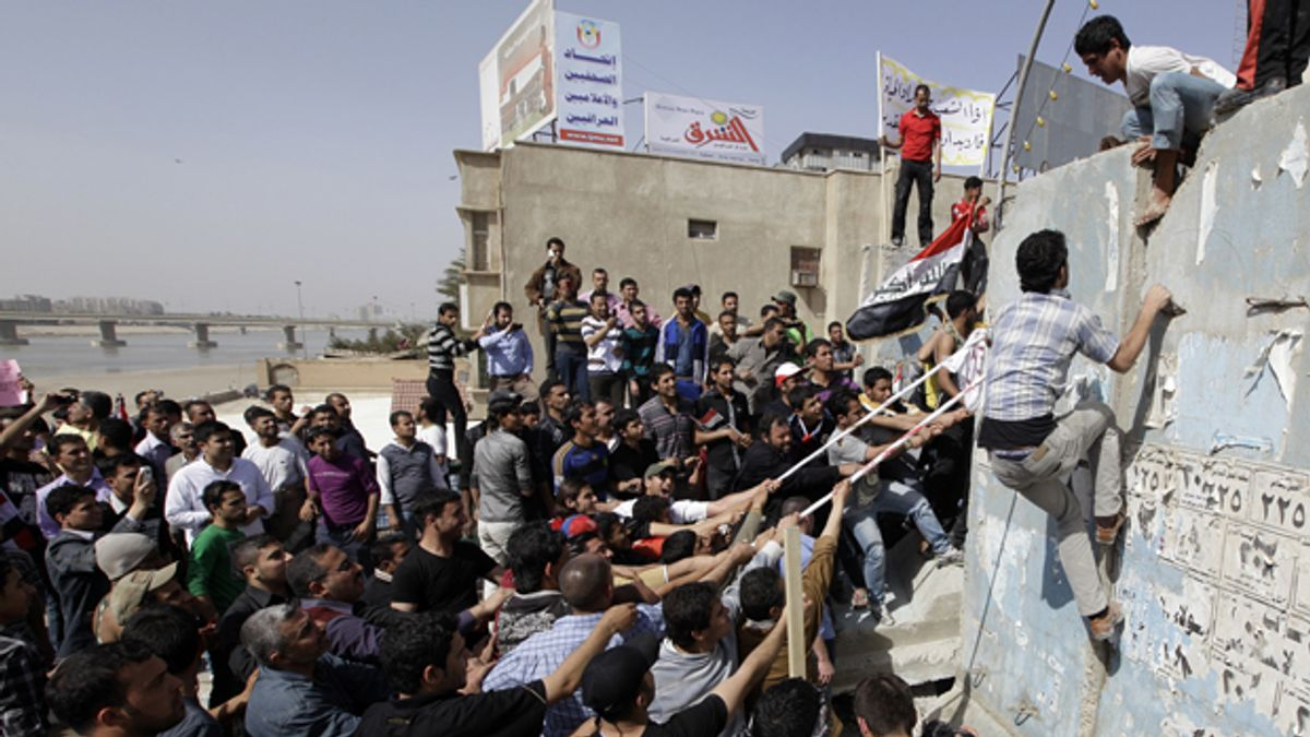 """Protesters pull down a concrete wall in Baghdad during Iraq's """"Day of Rage."""""""