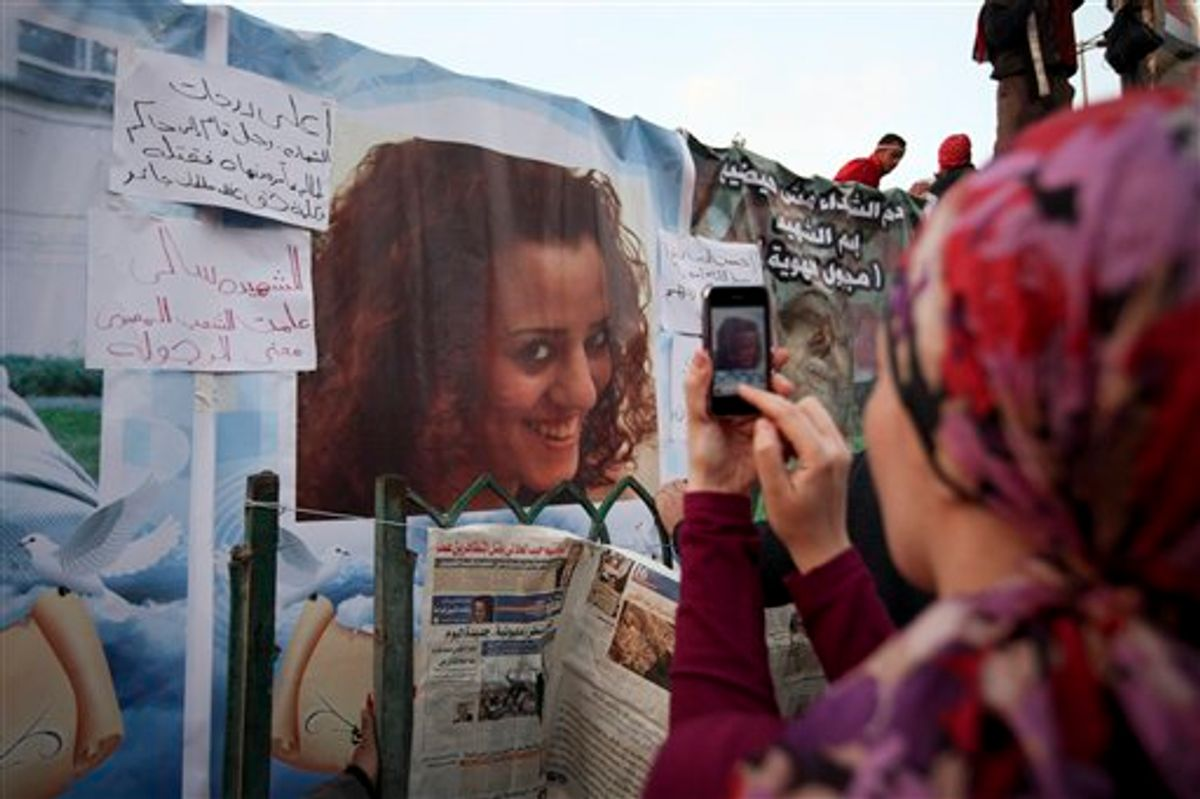 """An anti-government protester takes a picture of a poster of Sally Zahran, age 23, who was killed in southern Egypt last month during clashes, in Tahrir Square, in Cairo, Egypt, Tuesday, Feb. 8, 2011. Faces of some of the hundreds killed in Egypt's two-week-old uprising are beginning to emerge from the fog of chaos. Details of the lives lost have started to appear in Egyptian newspapers, on websites and in huge posters put up in Cairo's Tahrir Square, the center of the revolt that erupted Jan. 25. The paper next to the photo reads in Arabic """"Sally the martyr. She taught Egyptian people the meaning of manhood"""". (AP Photo/Tara Todras-Whitehill) (AP)"""
