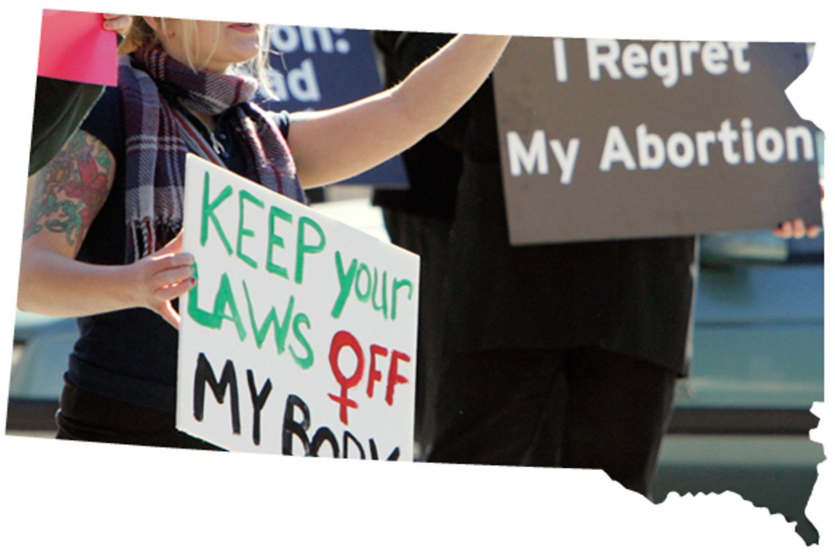 """A demonstrator holds up a pro-choice sign, left, as an opposing demonstrator holds up sign reading """"I Regret My Abortion"""", during a rally in downtown Sioux Falls, S.D."""