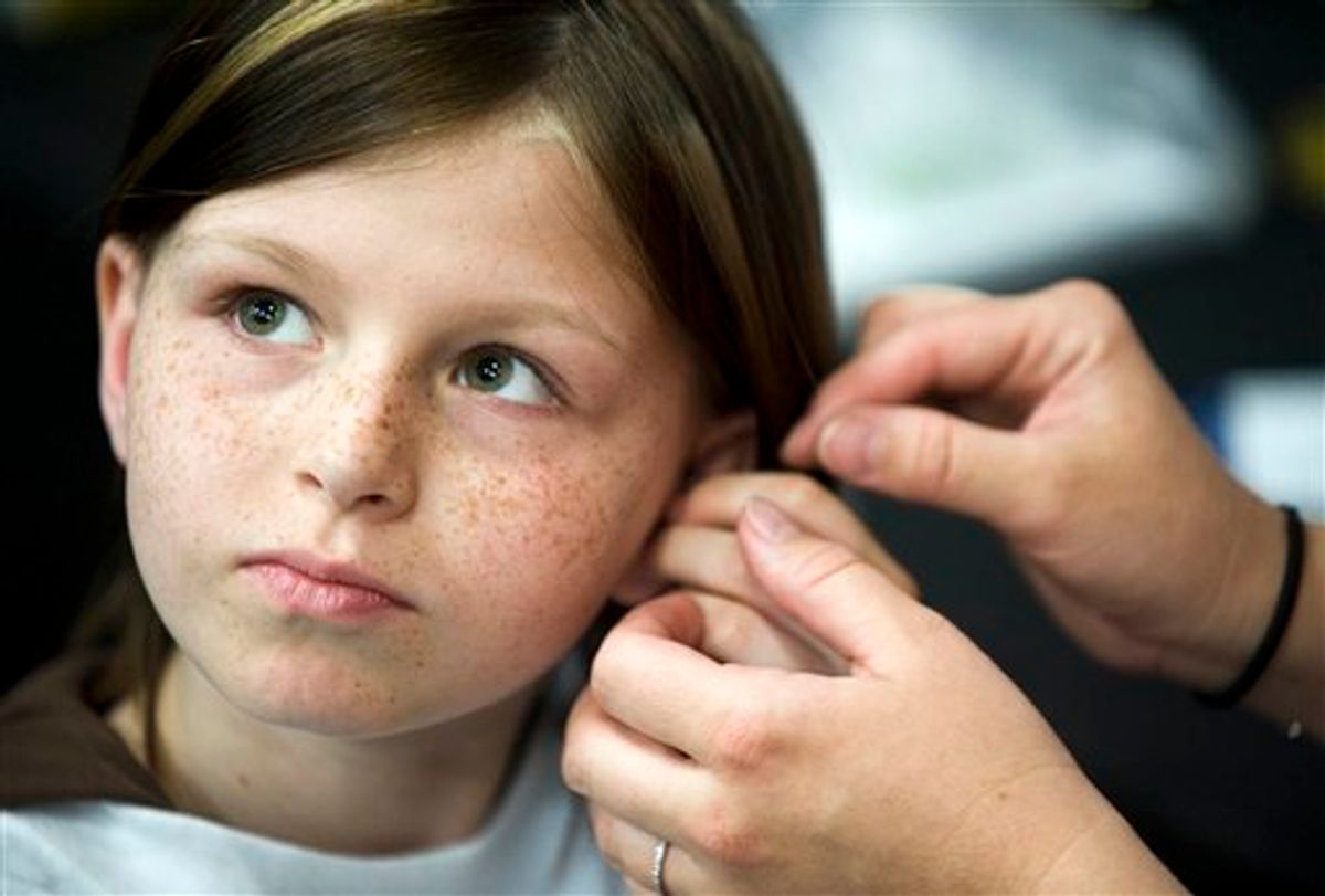 FILE -This May 2010 file photo shows Zahra Clare Baker, 10, getting a hearing aid during an event at Charlotte Motor Speedway in Hickory, N.C. Elisa Baker , stepmother of Zahra Clare Baker, was indicted Monday, Feb. 21, 2011 on a second-degree murder charge in Zahra Clare Baker's death. Elisa Baker had previously been charged with obstructing justice in the investigation of Zahra Baker's death. The 10-year-old was reported missing in October, and police later found her remains in different locations in western North Carolina. (AP Photo/The Independent Tribune, James Nix, File) (AP)
