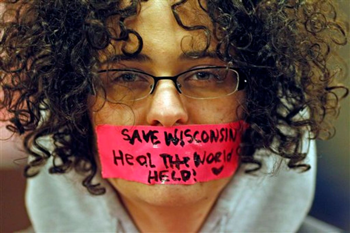 Kathryn Schulze wears a message written on tape over her mouth inside the state Capitol Monday, Feb. 21, 2011, in Madison, Wis. Opponents to Governor Scott Walker's bill to eliminate collective bargaining rights for many state workers are taking part in their seventh day of protesting. (AP Photo/Jeffrey Phelps)  (AP)