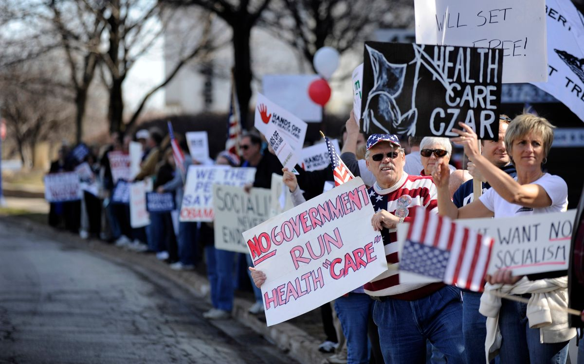 Protesters hold signs and yell at passing cars during a tea party protest against the proposed health care plan outside the office of Rep. Melissa Bean, D-Ill., in Schaumburg, Ill. on Tuesday, Mar. 16, 2010. (AP Photo/Paul Beaty) (Paul Beaty)
