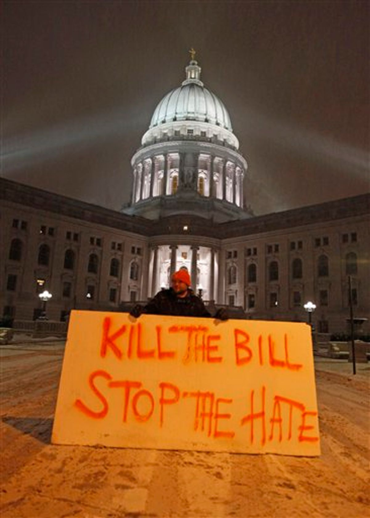 Luke Balsavich holds a large sign outside the state Capitol Monday, Feb. 21, 2011, in Madison, Wis. Opponents to Governor Scott Walker's bill to eliminate collective bargaining rights for many state workers are taking part in their seventh day of protesting.  (AP Photo/Jeffrey Phelps)  (AP)