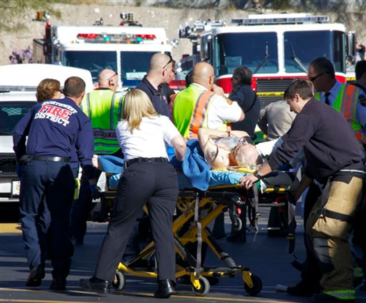 Emergency personnel attend to a shooting victim  outside a shopping center in Tucson, Ariz. on Saturday, Jan. 8, 2011 where U.S. Rep. Gabrielle Giffords, D-Ariz., and others were shot as the congresswoman was meeting with constituents.  (AP Photo/James Palka) (AP)