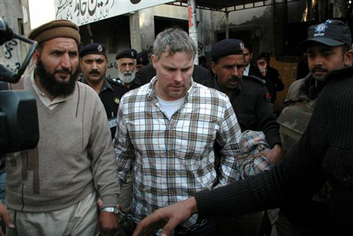 FILE - In this Jan. 28, 2011 file photo, Pakistani security officials escort Raymond A. Davis a U.S. consulate employee, center, to a local court in Lahore, Pakistan.  Most legal experts in Pakistan's government believe an American detained in the killing of two Pakistanis has diplomatic immunity, but a court should decide his fate, an official said Tuesday Feb. 15, 2011. The announcement reflected an apparent bid to open the way to the man's release while dampening public outrage. (AP Photo/Hamza Ahmed, File) (AP)