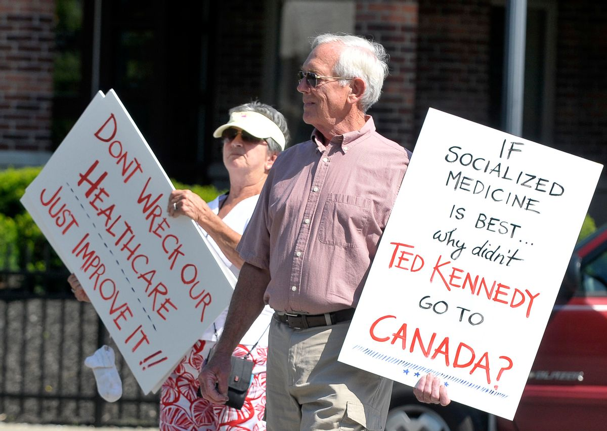 Elizabeth Smith ,left, and her husband Spence Smith hold protest signs during a rally protesting goverment managed health care in Saratoga Springs, N.Y., Thursday, August 6, 2009. (AP Photo/Hans Pennink) (Hans Pennink)