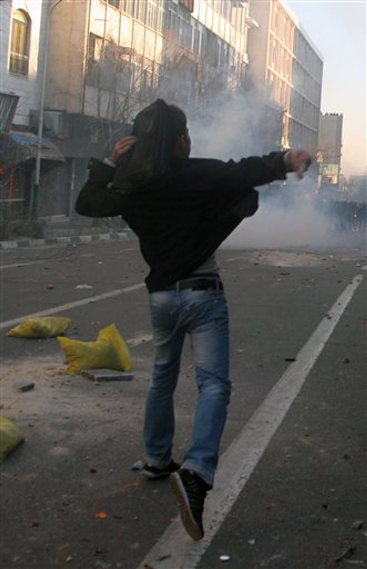 """This photo, taken by an individual not employed by the Associated Press and obtained by the AP outside Iran shows an Iranian protestor throwing stone at ant-riot police officers, during an anti-government protest in Tehran, Iran, Monday, Feb. 14, 2011. Eyewitnesses report that sporadic clashes have erupted in central Tehran's Enghelab or Revolution square between security forces and opposition protesters. The demonstrators were chanting """"death to the dictator,"""" referring to the country's hardline president that the opposition believes was reelected through fraud in 2009. (AP Photo) EDITORS NOTE AS A RESULT OF AN OFFICIAL IRANIAN GOVERNMENT BAN ON FOREIGN MEDIA COVERING SOME EVENTS IN IRAN, THE AP WAS PREVENTED FROM INDEPENDENT ACCESS TO THIS EVENT (AP)"""