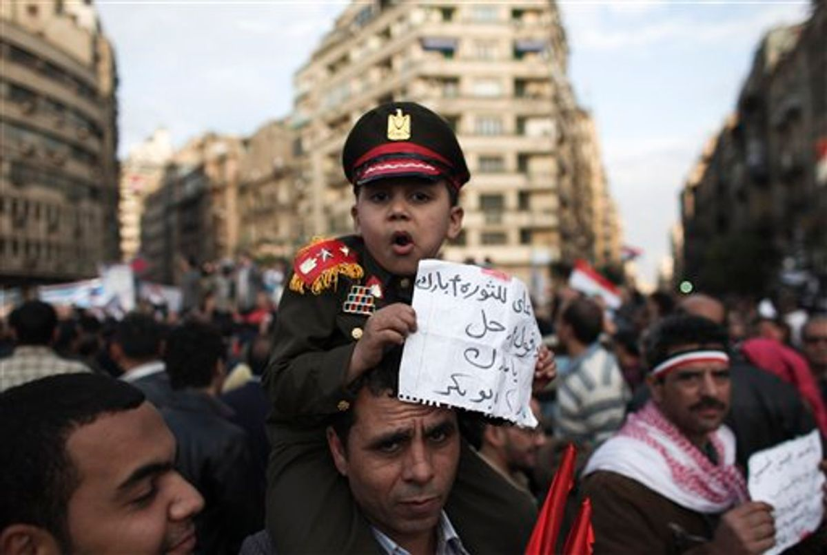 """An Egyptian boy dressed as an army colonel sits on his father's shoulders in Tahrir Square in Cairo, Egypt, Thursday, Feb. 10, 2011. President Mubarak refused to step down or leave the country and instead handed his powers to his vice president Thursday, remaining president and ensuring regime control over the reform process, which stunned protesters demanding his ouster, who waved their shoes in contempt and shouted, """"Leave, leave, leave."""" The arabic on the paper reads """"I came to give my blessings to the revolution and tell Mubarak to go"""". (AP Photo/Tara Todras-Whitehill) (AP)"""