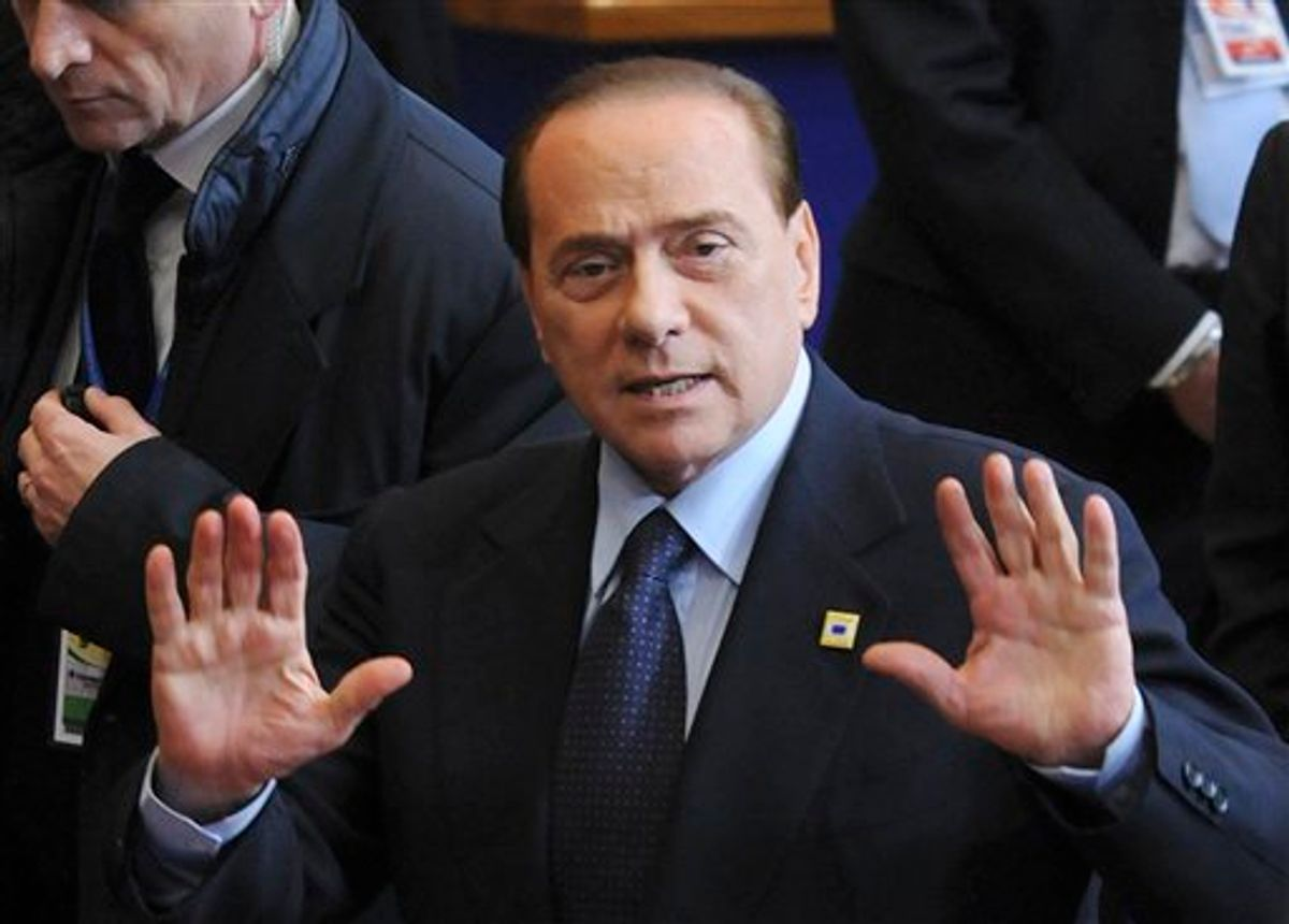 Italy's Prime Minister Silvio Berlusconi motions to the media as he leaves an EU summit in Brussels, Friday, Feb. 4, 2011. EU leaders meet for a one-day summit on Friday, with energy, the eurozone debt crisis and unrest in Egypt set to dominate the agenda. (AP Photo/Thierry Charlier) (AP)
