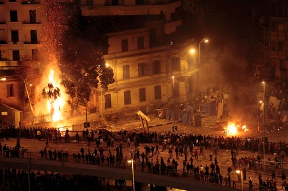 Pro-government demonstrators, bottom, clash with anti-government demonstrators, top right, as a palm tree burns from a firebomb, in Tahrir Square, the center of anti-government demonstrations, in Cairo, Egypt, early Thursday, Feb. 3, 2011. Thousands of supporters and opponents of Egyptian President Hosni Mubarak battled in Cairo's main square all day Wednesday, raining stones, bottles and firebombs on each other in scenes of uncontrolled violence as soldiers stood by without intervening. Government backers galloped in on horses and camels, only to be dragged to the ground and beaten bloody. (AP Photo/Lefteris Pitarakis) (AP)