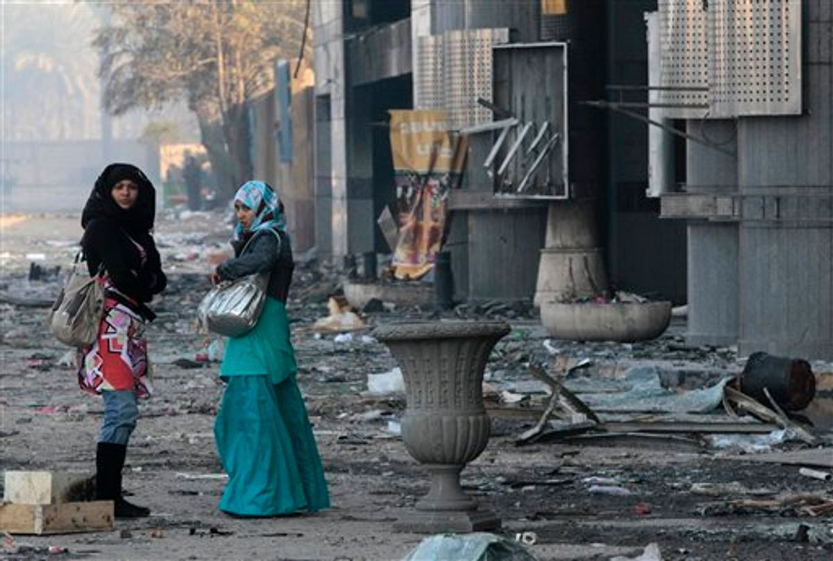 Women walk past a damaged shopping center in Cairo, Egypt, Monday, Jan. 31, 2011. Police and garbage collectors appeared on the streets of Cairo Monday morning and subway stations reopened after soldiers and neighborhood watch groups kept the peace in many districts overnight. (AP Photo/Lefteris Pitarakis) (AP)