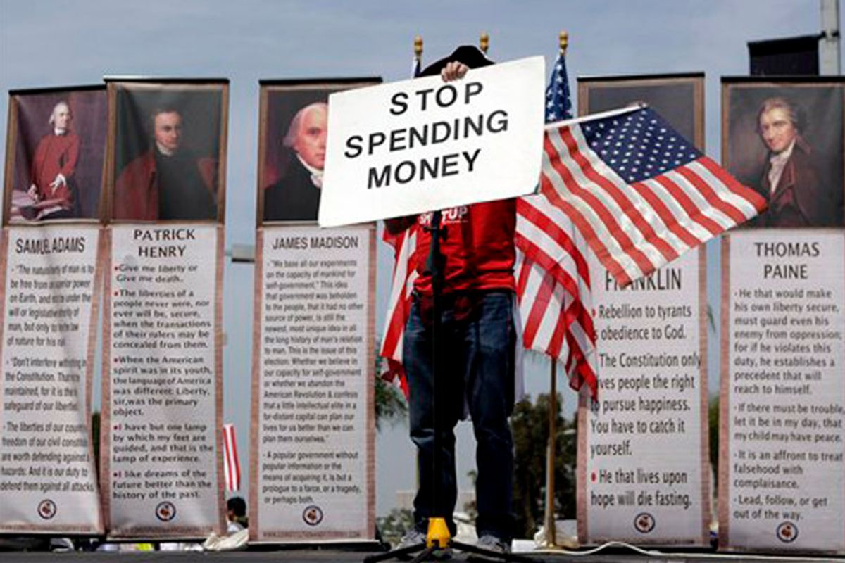 """Michael Fell, of Culver City, Calif., holds up a sign reading """"STOP SPENDING MONEY"""" as he speaks at a tea party rally in Irvine, Calif., Thursday, April 15, 2010. (AP Photo/Jae C. Hong) (Jae C. Hong)"""