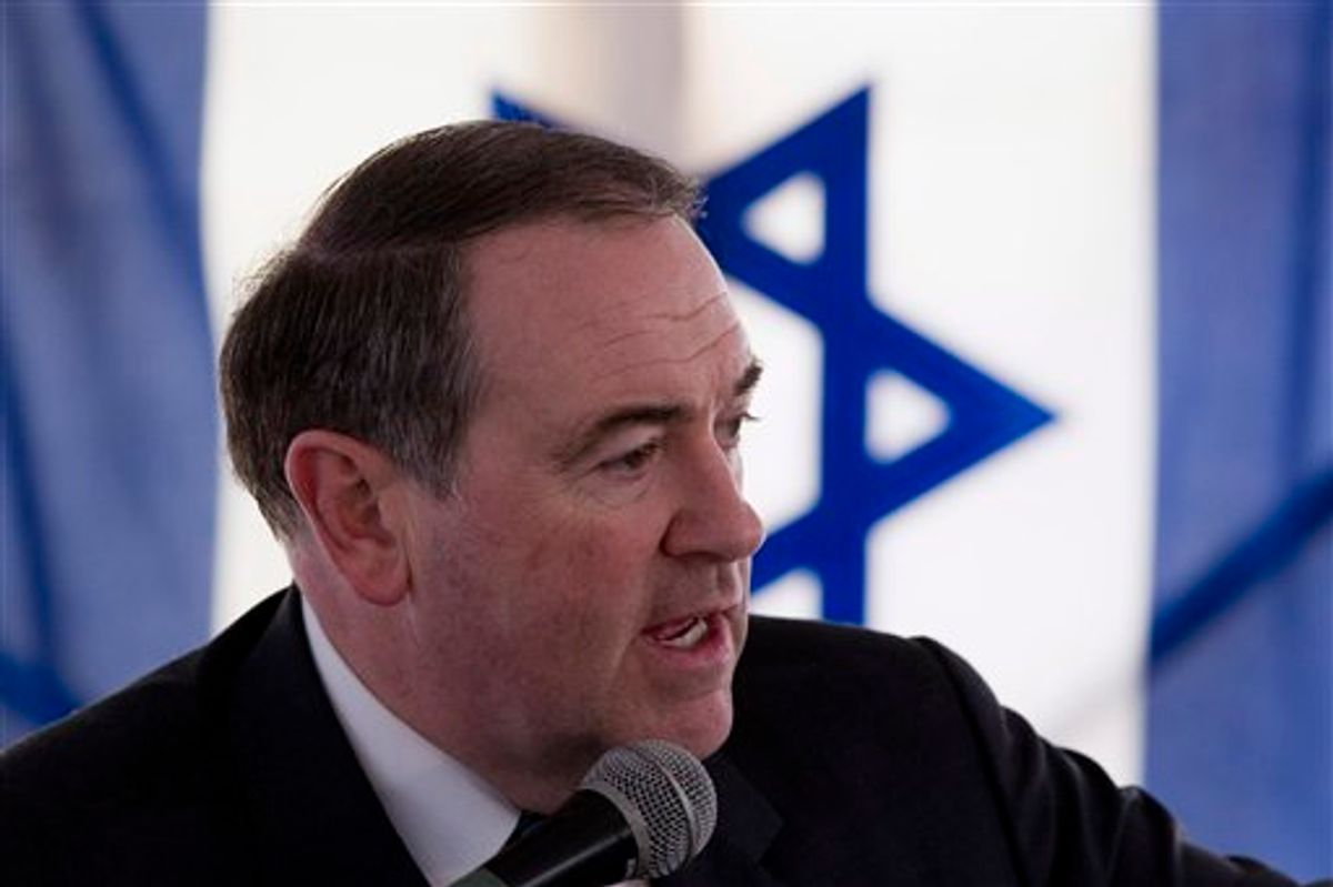 With an Israeli flag in the background, former Arkansas Gov. and Republican presidential contender Mike Huckabee speaks in Beit Oron, east Jerusalem, Monday, Jan. 31, 2011. Likely 2012 U.S. presidential contender Mike Huckabee says preventing Jewish settlers from building in east Jerusalem is as outrageous as discriminating against Americans because of their race, language or religion. Huckabee spoke at the dedication of a new Jewish neighborhood in east Jerusalem, which is claimed by the Palestinians. (AP Photos/Bernat Armangue) (AP)