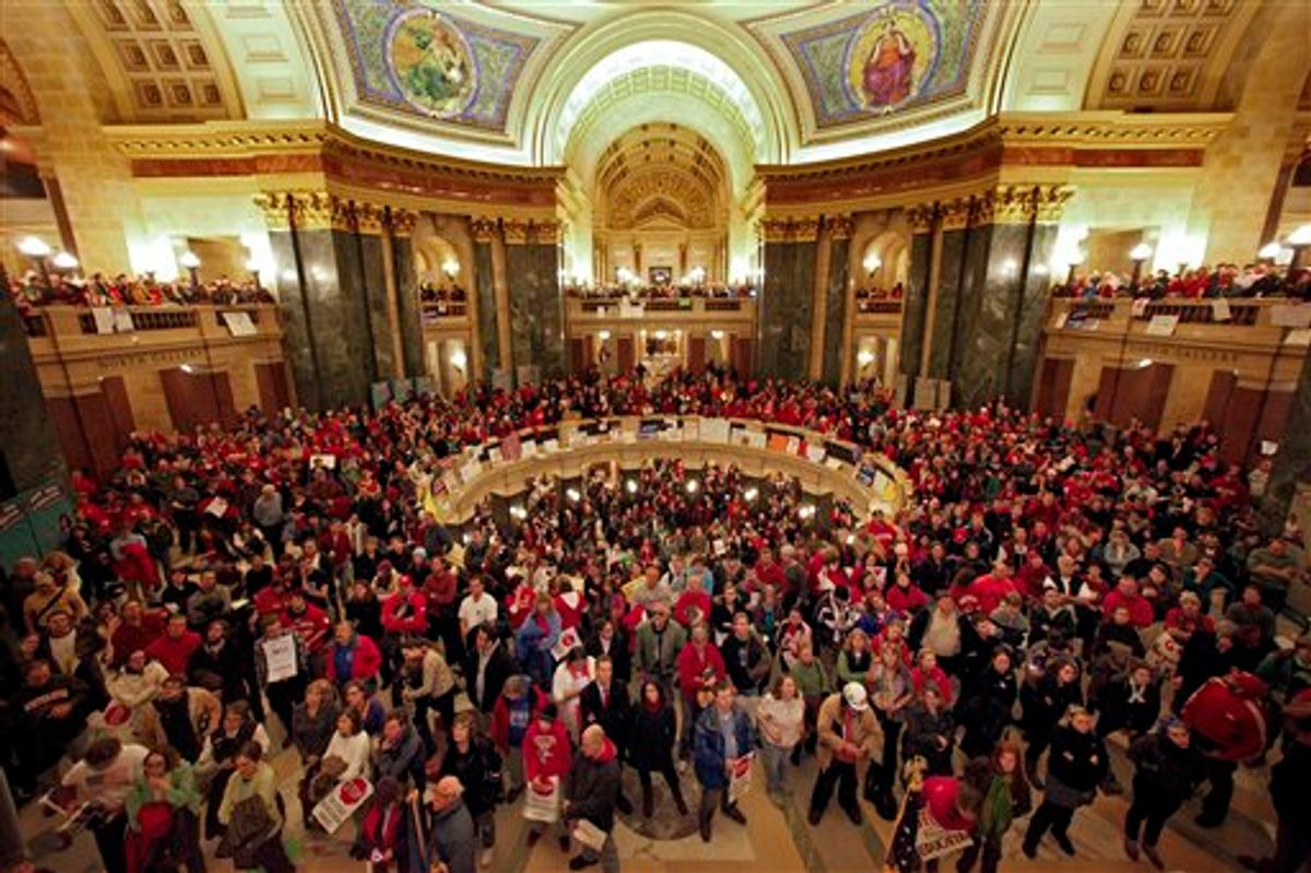 Protestors to Wisconsin Gov. Scott Walker's proposal to eliminate collective bargaining rights for many state workers listen in the rotunda at the State Capitol in Madison, Wis., Wednesday, Feb. 16, 2011, to testimony during a Joint Finance Committee meeting . (AP Photo/Andy Manis) (AP)
