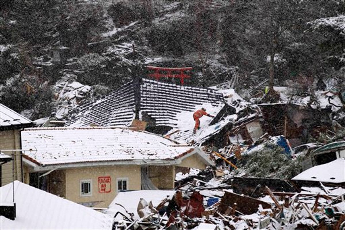 A member of a British search and rescue team climbs on the roof of a building damaged by the tsunami, whilst searching for trapped people as snow falls in Kamaishi, Japan, Wednesday, March 16, 2011. Two search and rescue teams from the U.S. and a team from the U.K. with combined numbers of around 220 personnel searched the town for survivors Wednesday to help in the aftermath of the earthquake and tsunami. (AP Photo/Matt Dunham) (AP)
