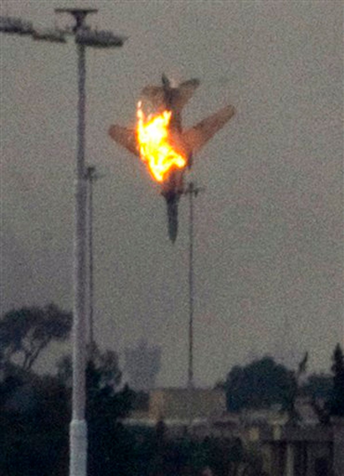 ALTERNATIVE CROP - A doomed warplane plummets towards earth after it was shot down by anti-Gadhafi forces over the outskirts of Benghazi, eastern Libya, Saturday, March 19, 2011.  An object, thought to be the pilot, was seen to eject from the cockpit shortly before impact.  Explosions shook the Libyan city of Benghazi early on Saturday while a fighter jet was heard flying overhead, and residents said the eastern rebel stronghold was under attack from  forces loyal to Libyan leader Moammar Gadhafi. (AP Photo/Anja Niedringhaus) (AP)