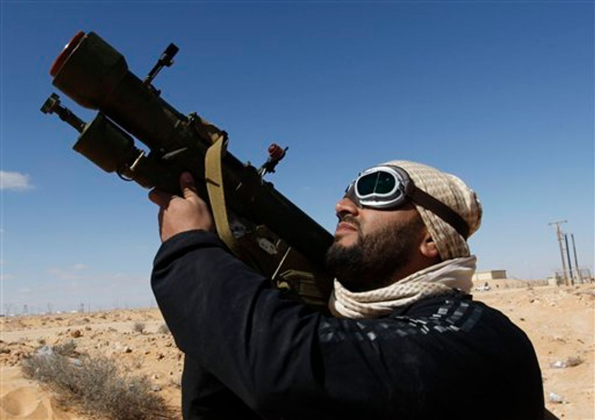 An anti-Libyan leader Moammar Gadhafi rebel, holds his anti-aircraft missile as he looks to the sky, in the oil town of Ras Lanouf, eastern Libya, Sunday, March 6, 2011. Thousands of Moammar Gadhafi's supporters poured into the streets of Tripoli on Sunday, waving flags and firing their guns in the air in the Libyan leader's main stronghold. Earlier, the city woke to the crackle of heavy machine-gun fire that rattled the capital before dawn.(AP Photo/Hussein Malla) (AP)