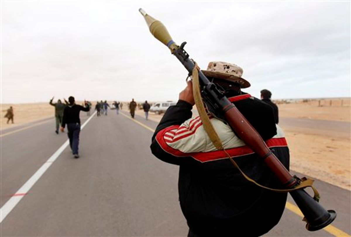 An anti-Gadhafi rebel, carries his RPG as he walks forward with other rebels to fight in the front line during fighting against pro-Gadhafi fighters, near the town of Bin-Jawad, eastern Libya, Tuesday, March 8, 2011. Libyan warplanes launched at least three new airstrikes Tuesday near rebel positions in the oil port of Ras Lanouf, keeping up a counteroffensive to prevent the opposition from advancing toward leader Moammar Gadhafi's stronghold in the capital Tripoli. (AP Photo/Hussein Malla) (AP)