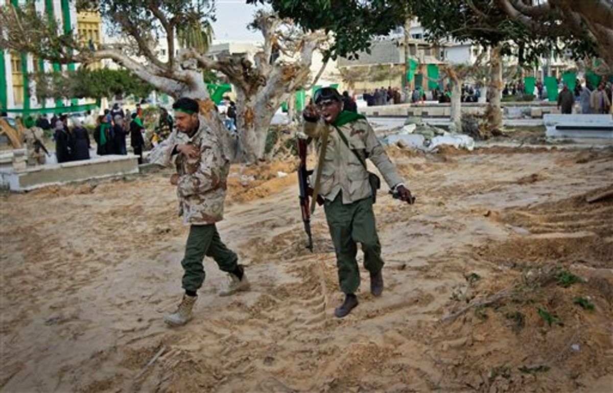In this photo taken during a government-organised visit for foreign media, a pro-Gadhafi soldier mimics a gun with his hand as he and another walk across freshly-bulldozed ground from which the bodies of opposition dead had been exhumed, according to a resident, in the main square of Zawiya, Libya Friday, March 11, 2011. Libyan Leader Moammar Gadhafi's regime has gained momentum with the capture of Zawiya after days of fierce fighting with rebels, in a key test of the government's ability to maintain its hold on the Libyan capital and surrounding areas. (AP Photo/Ben Curtis) (AP)