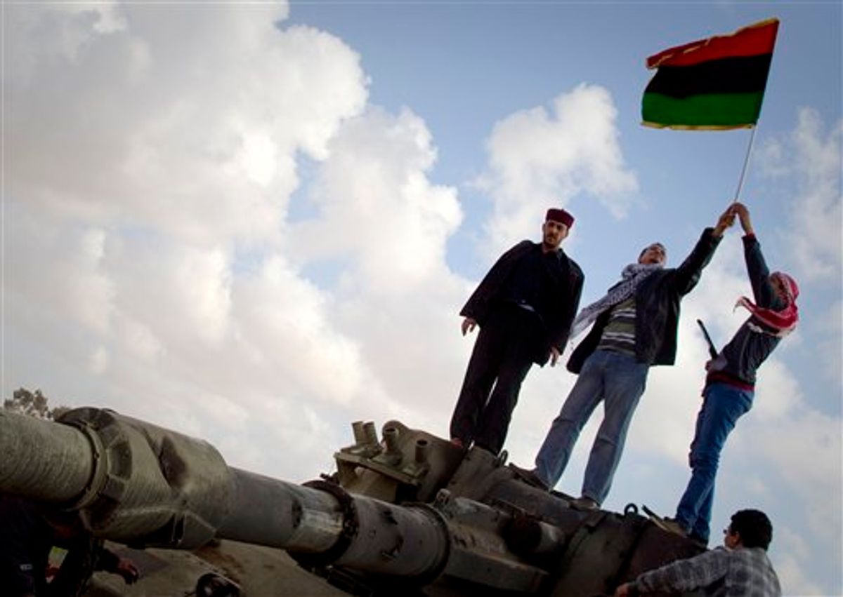Libyan men celebrates on a destroyed tank belonging to the forces of Moammar Gadhafi in the outskirts of Benghazi, eastern Libya, Sunday, March 20, 2011. The tanks were destroyed earlier by U.S. and allied airstrikes.  (AP Photo/Anja Niedringhaus) (AP)