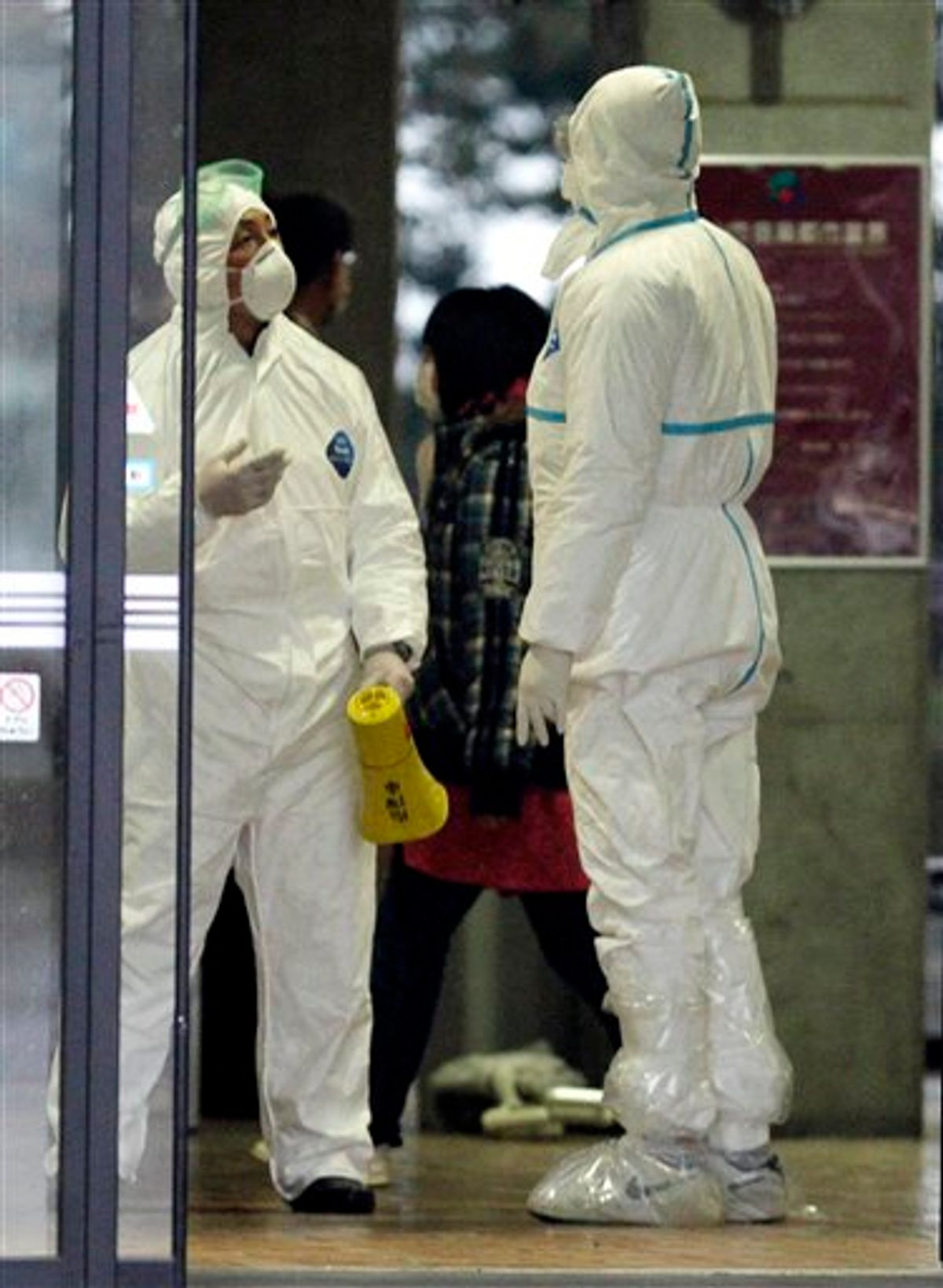Officials wearing protective suits chat as they usher people through a radiation emergency scanning center in Koriyama, Japan, Tuesday, March 15, 2011 four days after a giant quake and tsunami struck the country's northeastern coast. (AP Photo/Mark Baker) (AP)