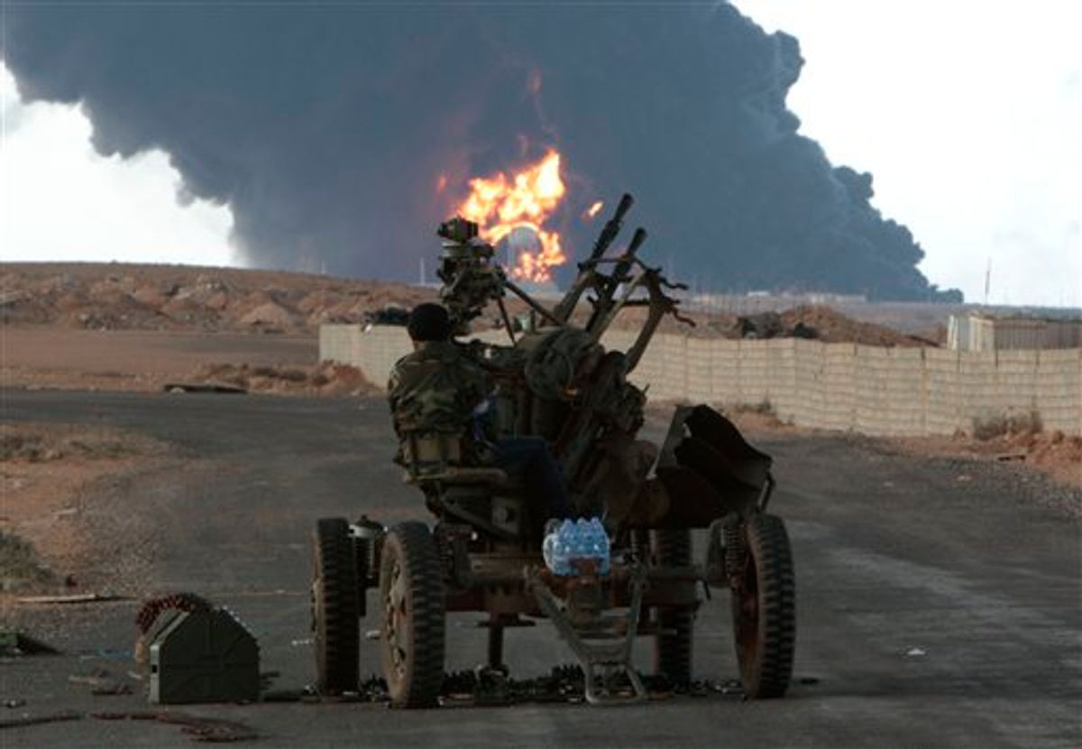Anti-Libyan Leader Moammar Gadhafi rebel, mans an anti-aircraft machine gun, as a pall of smoke and flames rises from a fuel storage depot that was attacked during fighting against pro-Moammar Gadhafi fighters, in Sedra, eastern Libya, on Wednesday March 9, 2011. Gadhafi appears to be keeping up the momentum he has seized in recent days in his fight against rebels trying to move on the capital, Tripoli, from territory they hold in eastern Libya. (AP Photo/Hussein Malla) (AP)