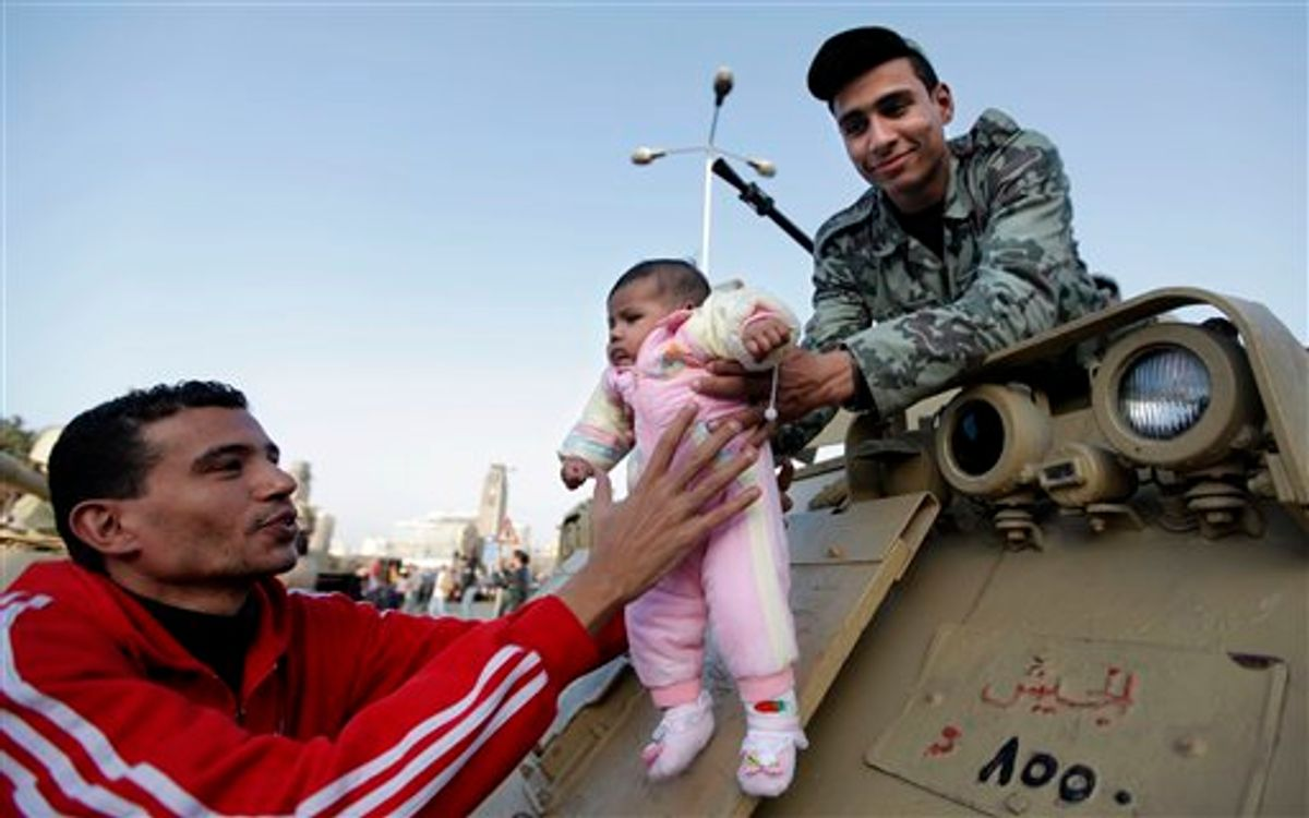 """An Egyptian man hands his child to an army soldier in order to take a picture of him on top of an army personal carrier during Friday demonstration at Tahrir square in Cairo, Egypt Friday, March 4, 2011. Egypt's new prime minister designate Essam Sharaf has vowed before thousands of mostly young demonstrators at a central Cairo square that he'll do everything he can to meet their demands, pleading they turn their attention to """"rebuilding"""" the country. (AP Photo/Nasser Nasser) (AP)"""