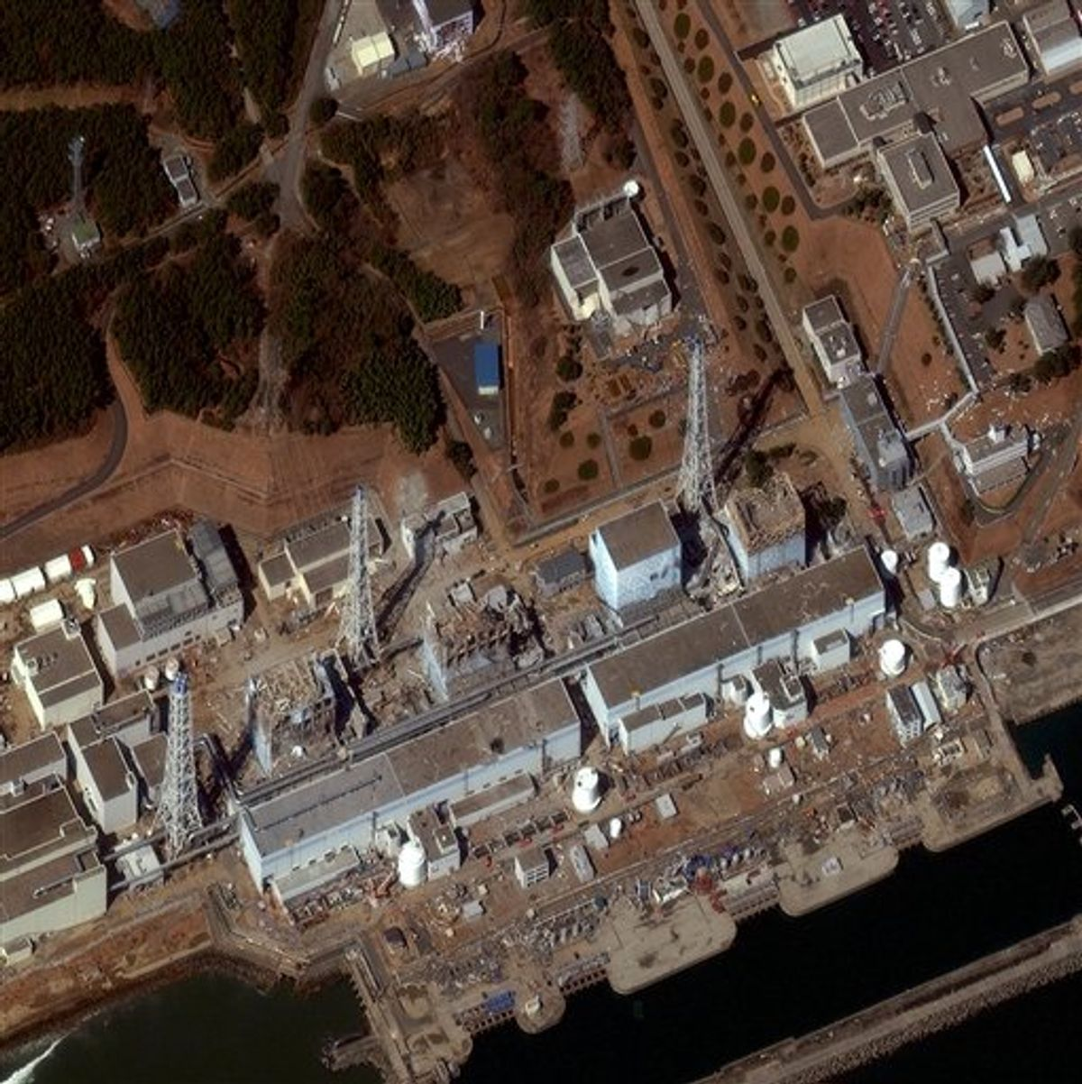 """In this Friday, March 18, 2011 satellite image released by DigitalGlobe, the Fukushima Dai-ichi is shown.  Sirens wailed Friday along a devastated coastline to mark exactly one week since an earthquake and tsunami triggered a nuclear emergency, and the government acknowledged it was slow to respond to the disasters that the prime minister called a """"great test for the Japanese people."""" The admission came as Japan welcomed U.S. help in stabilizing its overheated, radiation-leaking Fukushima Dai-ichi nuclear complex and raised the accident level for the crisis, putting it on a par with the 1979 Three Mile Island accident in Pennsylvania. (AP Photo/DigitalGlobe) NO SALES (AP)"""