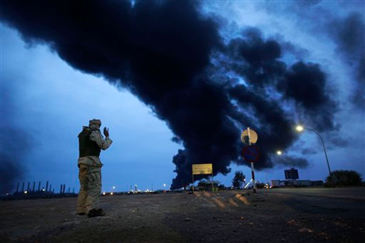 In this photo taken during a government-organised visit for foreign media, a pro-Gadhafi fighter makes his evening prayers in the desert as a plume of smoke rises from the burning oil refinery in Ras Lanouf, 380 miles (615 kilometers) southeast of the capital Tripoli, in Libya Saturday, March 12, 2011. (AP Photo/Ben Curtis) (AP)