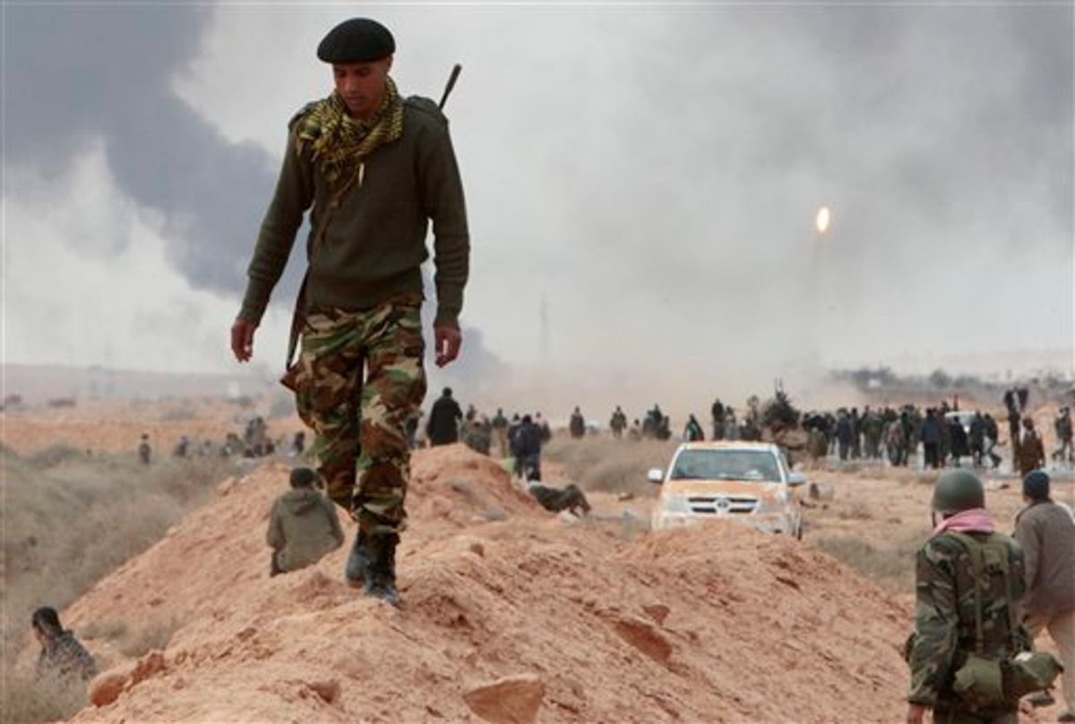 An anti-Gadhafi rebel, walks along a sand barrier, as other rebels fire a rocket launcher seen in the right, during  fighting against pro-Gadhafi fighters, in Sedra, eastern Libya, Wednesday March 9, 2011. A high-ranking member of the Libyan military flew to Cairo on Wednesday with a message for Egyptian army officials from Moammar Gadhafi, whose troops pounded opposition forces with artillery barrages and gunfire in at least two major cities. Gadhafi appeared to be keeping up the momentum he has seized in recent days in his fight against rebels trying to move on the capital, Tripoli, from territory they hold in eastern Libya. (AP Photo/Hussein Malla) (AP)