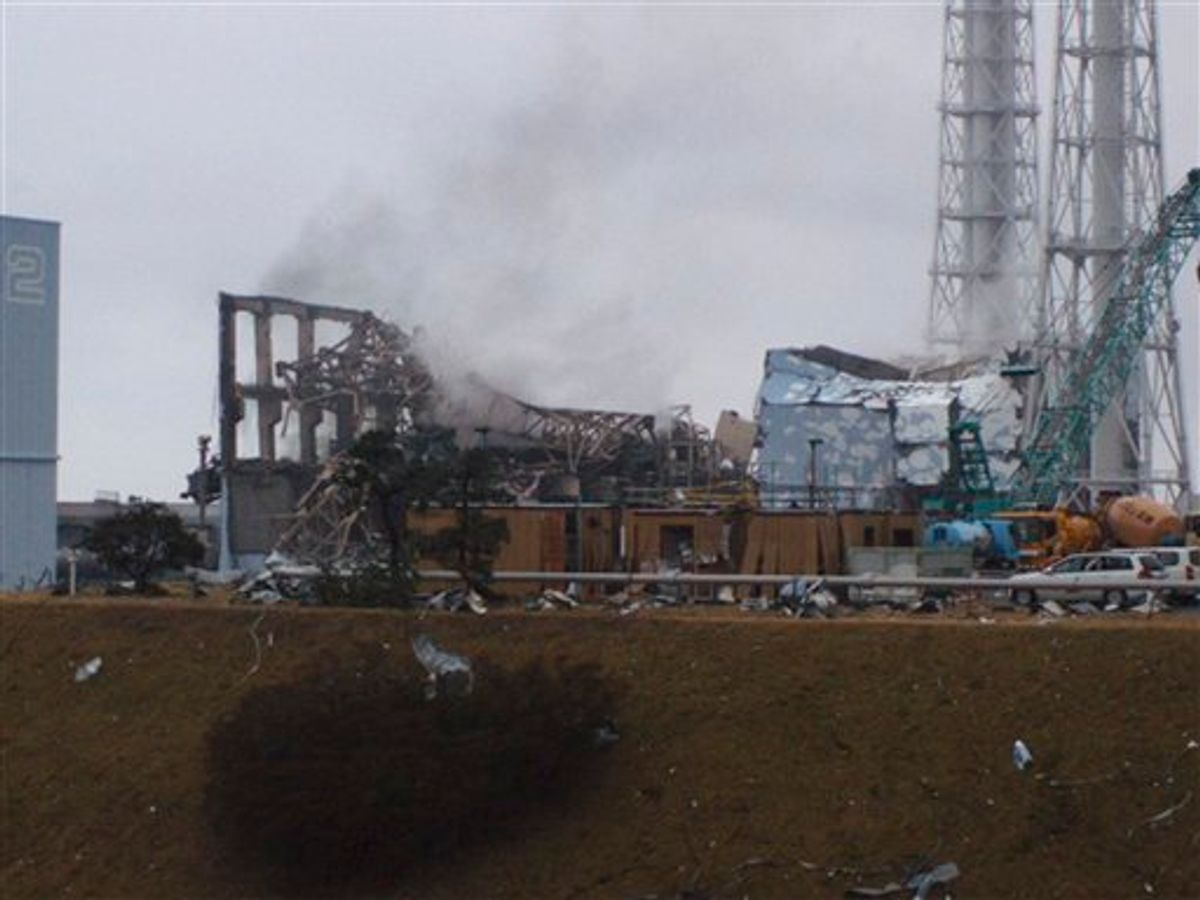 In this photo released by Tokyo Electric Power Co. (TEPCO), gray smoke rises from Unit 3 of the tsunami-stricken Fukushima Dai-ichi nuclear power plant in Okumamachi, Fukushima Prefecture, Japan, Monday, March 21, 2011. Official says the TEPCO temporarily evacuated its workers from the site. At left is Unit 2 and at right is Unit 4. (AP Photo/Tokyo Electric Power Co.) EDITORIAL USE ONLY (AP)