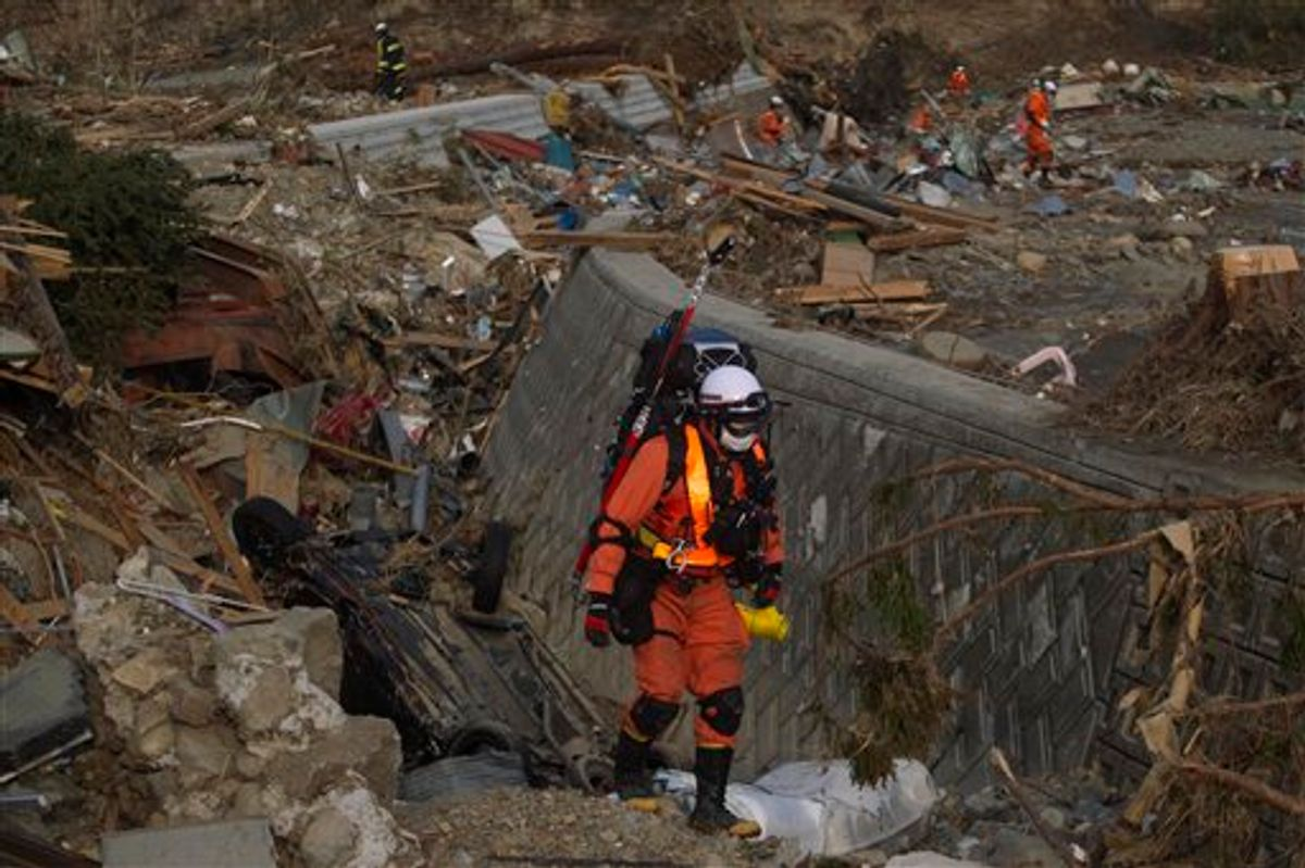 A Japanese rescue team member walks through the completely leveled village of Saito, in northeastern Japan, Monday, March 14, 2011. (AP Photo/David Guttenfelder) (AP)