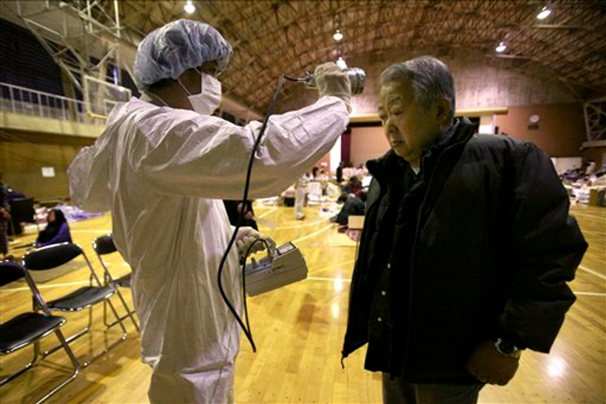 A man is screened for radiation exposure at a shelter after being evacuated from areas around the Fukushima nuclear facilities damaged by last week's major earthquake and following tsunami, Wednesday, March 16, 2011, in Fukushima city, Fukushima prefecture, Japan. (AP Photo/Wally Santana) (AP)