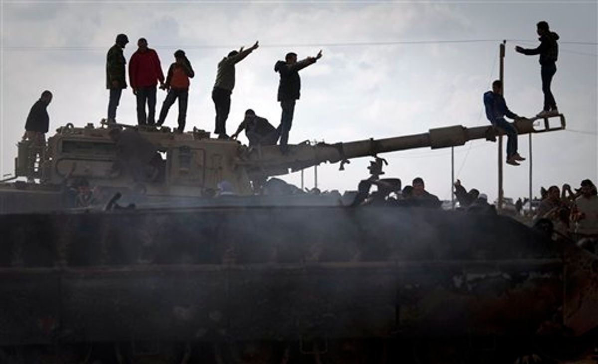 Libyan people celebrate on a tank belonging to the forces of Moammar Gadhafi in the outskirts of Benghazi, eastern Libya, Sunday, March 20, 2011. The tanks were destroyed earlier by NATO plans. (AP Photo/Anja Niedringhaus) (AP)